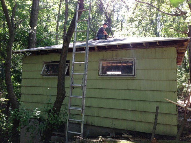Installing shingles on the lesser seen sides of the barn first.