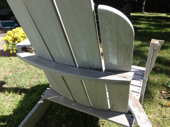 Busted adirondack chair with a missing arm and broken back brace.