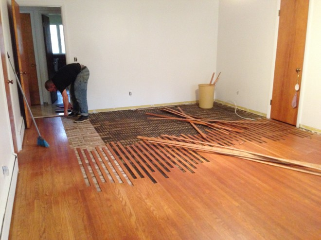 Removing the oak floorboards one at a time.