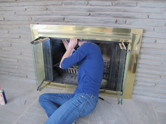 Removing the gold fireplace cover.