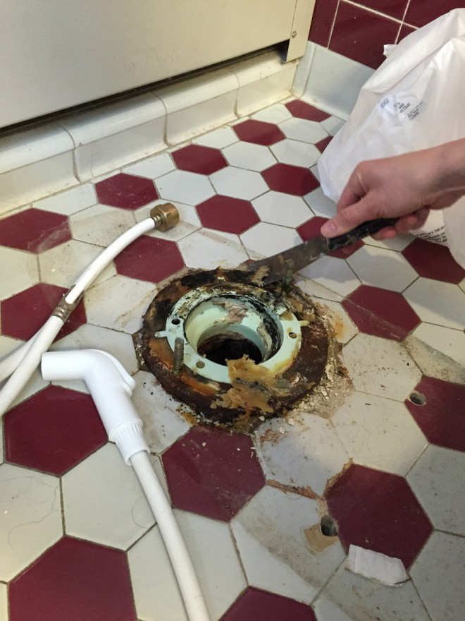 Removing wax and inspecting a floor flange during the toilet replacement.