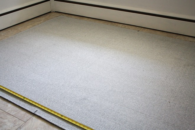 Measuring a rug to be custom cut into a half-circle.