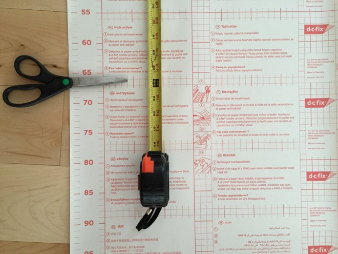Measure and cut pieces of adhesive wallpaper to install.