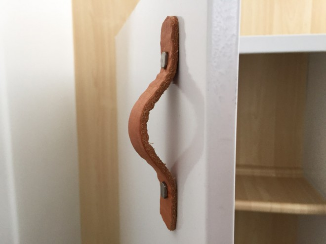 Attaching a leather belt to a cabinet for a unique door pull.