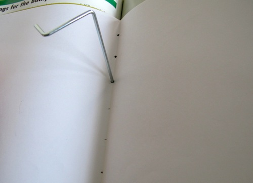 Stitching the binding of a DIY paper book.