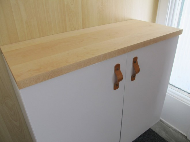 Attaching a wooden countertop to a metal sideboard.