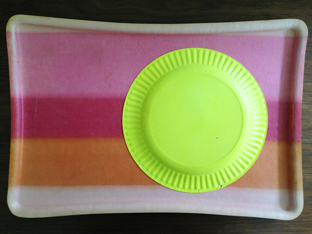 Paint a paper plate with yellow paint.