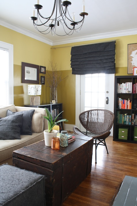 Painting two colors with a horizontal line break in a living room – greens and golds.