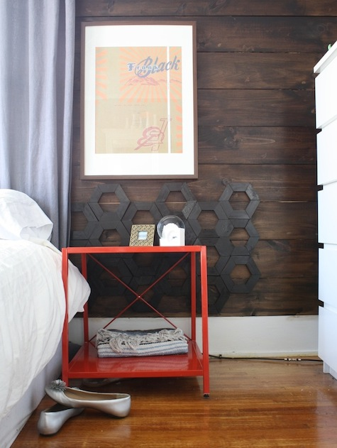 A DIY headboard using shiplap and hexagon-shaped accents.