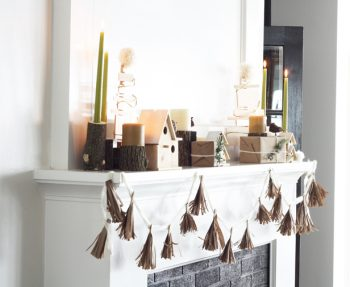 Style a natural, modern holiday mantel for your home using kraft paper, wooden accents, and pine branches.