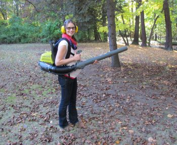 Pregnant Emily using a leaf blower.