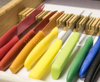 Rainbow knifes in a DIY knife rack using a piece of scrap wood.
