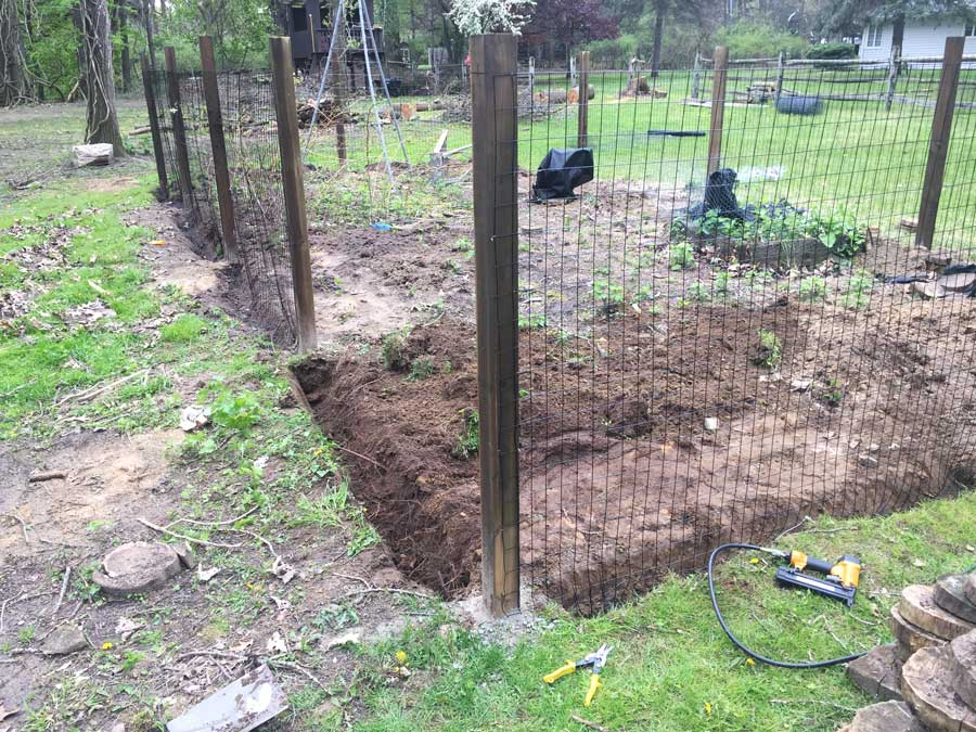 Installing steel fencing panel by panel for our new garden.