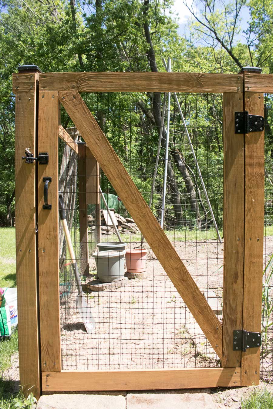 DIY garden fence constructed with self-closing hinges and designed for kids to access.