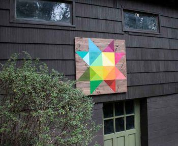 Modern, rainbow-colored barn quilt on our mid-century home's outbuilding.