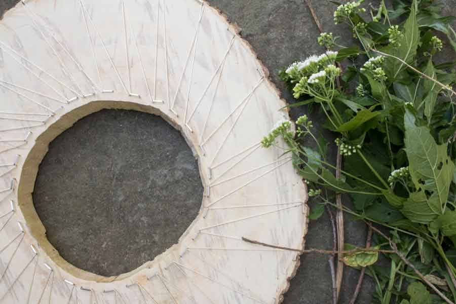 How to make an always-changing wreath by using a log cross section as a base for a loom.
