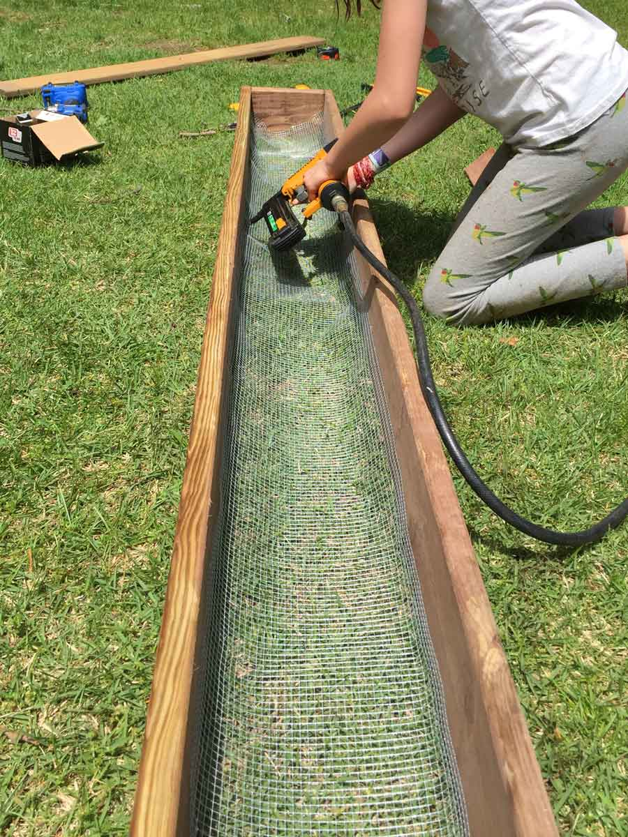 Building a DIY planter box with a steel mesh bottom, to allow for drainage and root health.