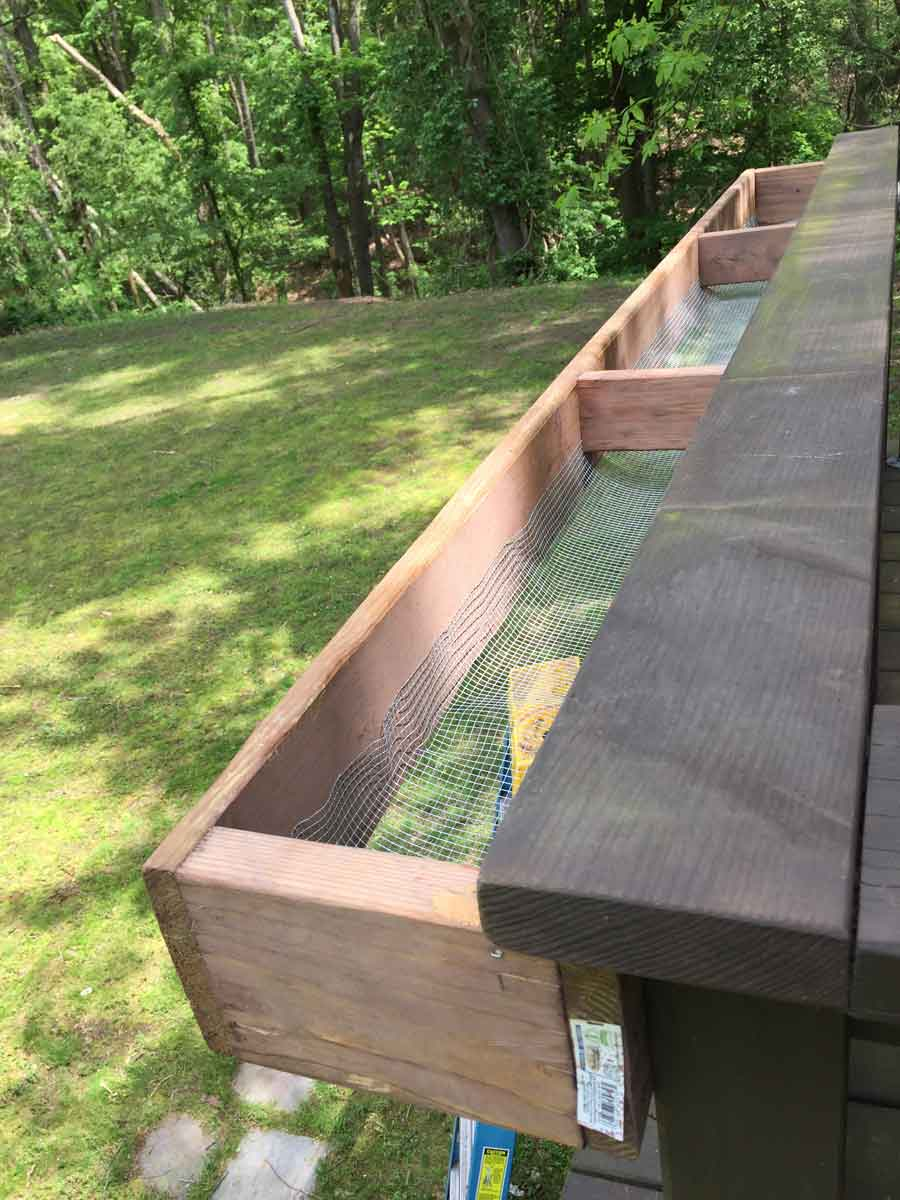 Attaching an 8-foot window box to a treehouse railing for a raised planter area.
