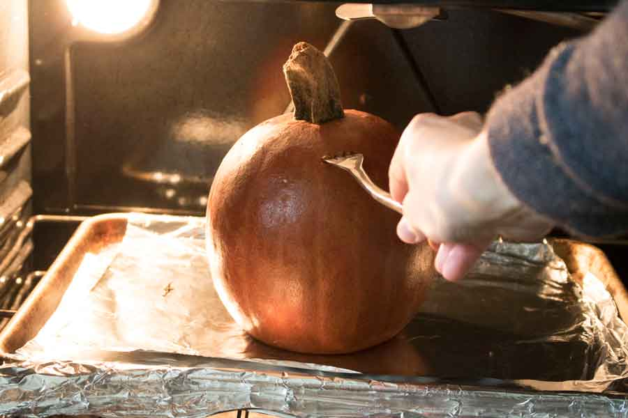 Poke a pumpkin to know if it's done baking in the oven.