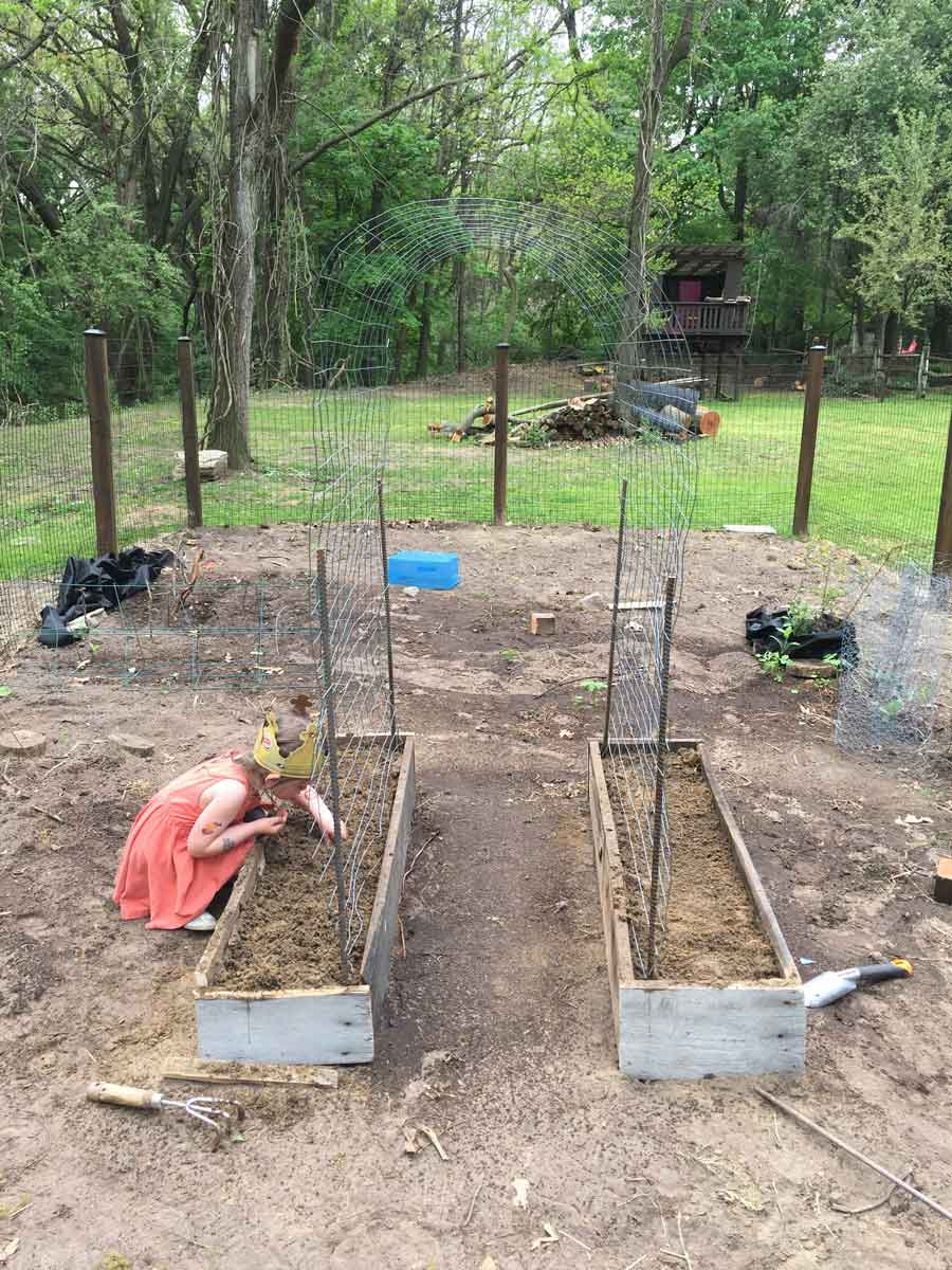 Teaching kids to plant and harvest vegetables in their own trellis archway garden.