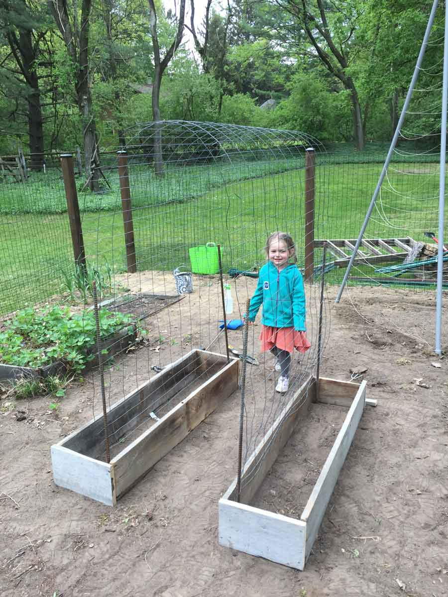 Building raised garden planter boxes from barn wood for an archway trellis.