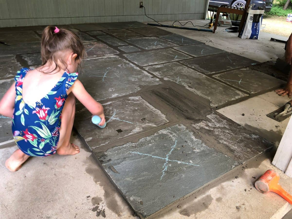 "Child marking ""X"" on flagstone tiles to prevent stepping on wet mortar."