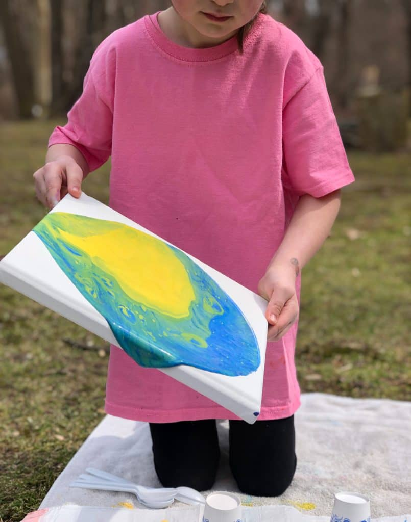 Pour art adapted for young kids makes use of washable craft paints and pouring medium.
