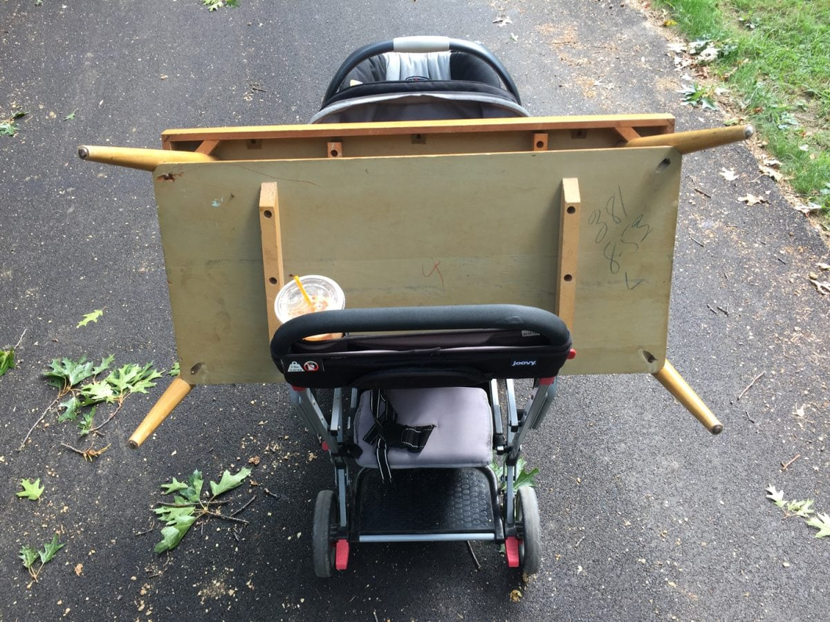 Carrying a mid-century coffee table home balanced on a stroller.