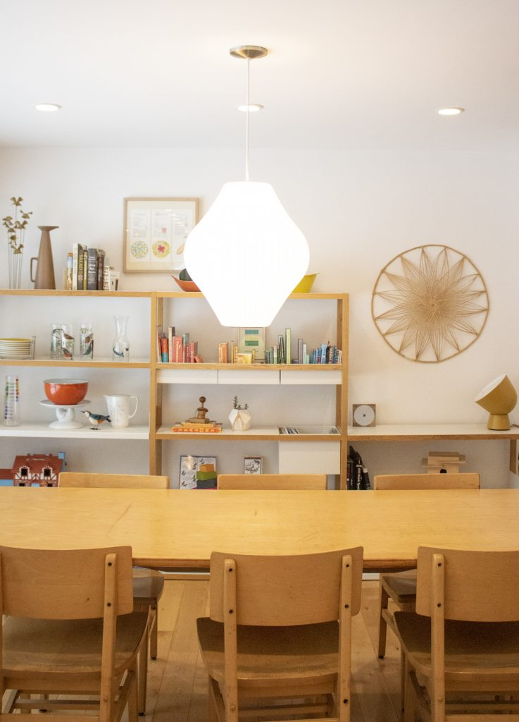 White walled dining room with vintage table, midcentury accents, and modern shelving.